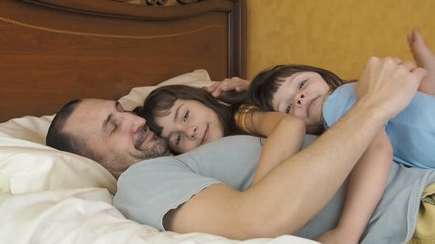 Father's daughters. Father's Day. Happy family in the bedroom. The girl hugs her father.