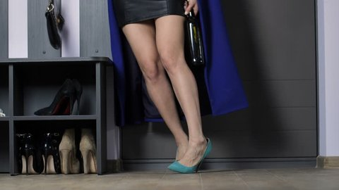 Legs of alcoholic drunken woman in mini skirt and high heels entering door with wine bottle in hand. Intoxicated female holding alcohol bottle throwing coat to the floor and walking to bed stumbling