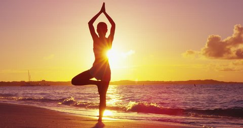 Yoga woman training in sunset in tree pose meditating outdoors on beach ocean sea. Female yoga instructor working out training in serene ocean landscape. Silhouette of woman model against sun.