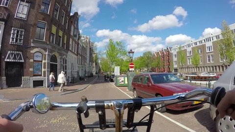 Amsterdam, Netherlands.. May 1, 2015. Bicycle ride across canals of Amsterdam. Point of view shot. Sunny day.