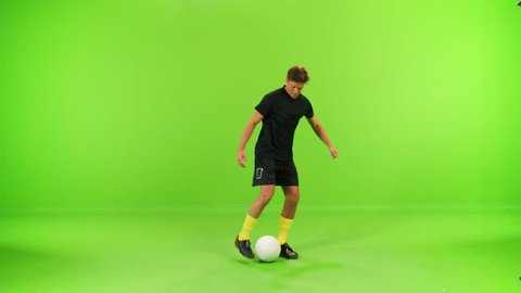 Soccer player juggling with a ball in a full shot over a green screen, high speed shutter, slow motion.