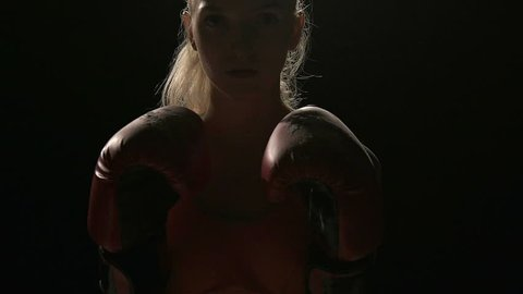 Woman ready to fight. Punches her gloves together to create powder smoke. White young beautiful fit woman. Shot in slow motion. Film look filter.