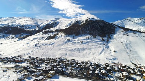Aerial view of Italian Alps in snowy winter, mountain peaks and ski slopes covered with snow, sunny day with clear blue sky - ski resort Livigno, Lombardy, Italy from above, 4k UHD