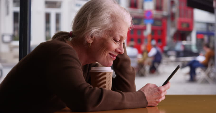 Happy senior woman receives good news via text while waiting in coffee shop. Smiling retiree using smartphone in cafe and drinking coffee. 4k