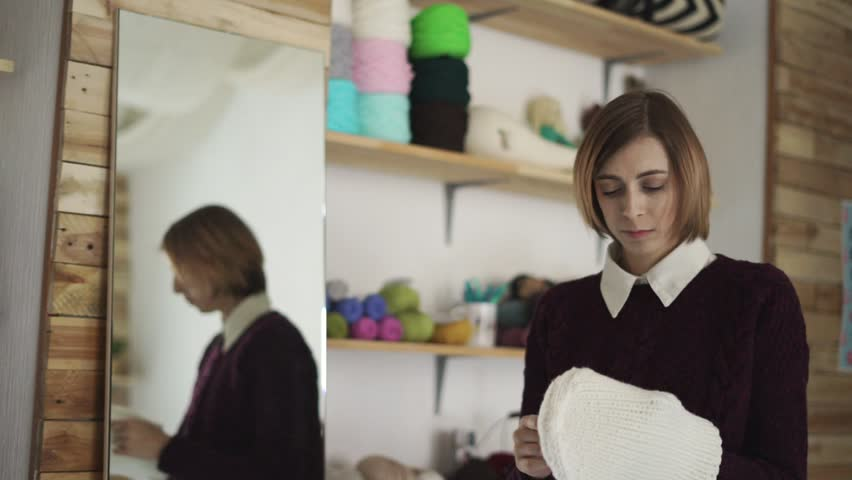 Unhappy woman standing with knitted hat near mirror in retail store. Sad woman holding knitted headdress in hand in show room. Dissatisfied consumer.