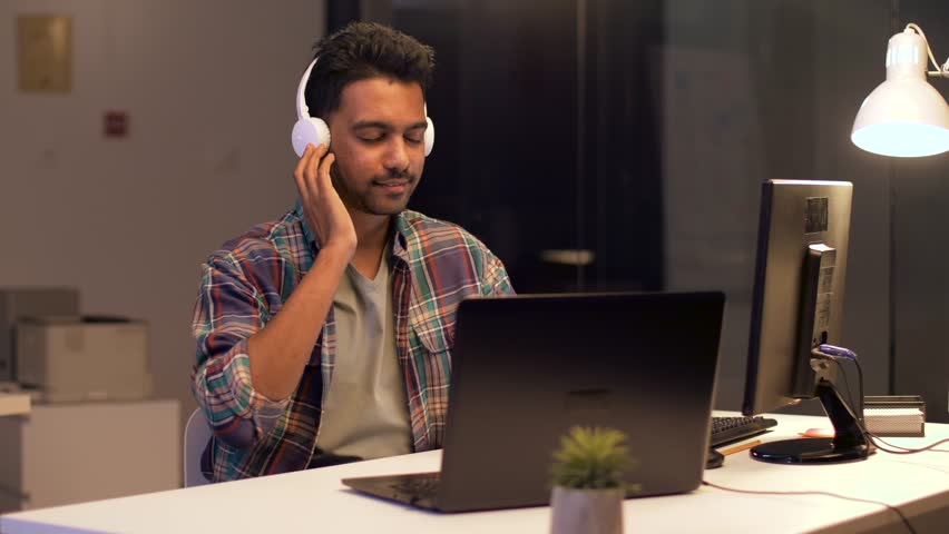 Deadline, technology and people concept - happy creative man with headphones and computer listening to music and working at night office | Shutterstock HD Video #1008563707