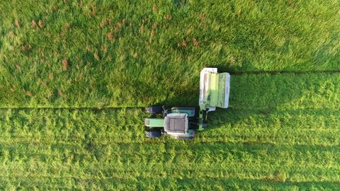 Aerial top down view of tractor cutting grass moving from right to left beautiful fresh green field meadow pasture the cut grass will be dried and become hay and then used as animal silage 4k quality