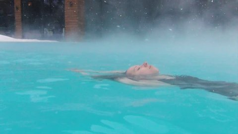 Young woman enjoying bathing relaxed in hot spa blue water