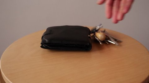Taking Keys ,wallet and smartphone to little table and Taking them from table . Arriving / Leaving Home concept.Slow motion