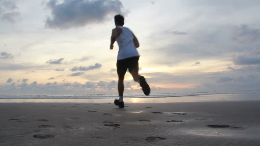 young sport man running on the beach in sunset A hand of a man texting on a handphone