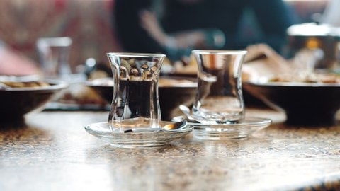 The waiter pours the eastern tea in cups. Close up