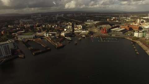 Cardiff Aerial backward motion over Bay, city centre with docks and museum, Cardiff millennium stadium in distance.