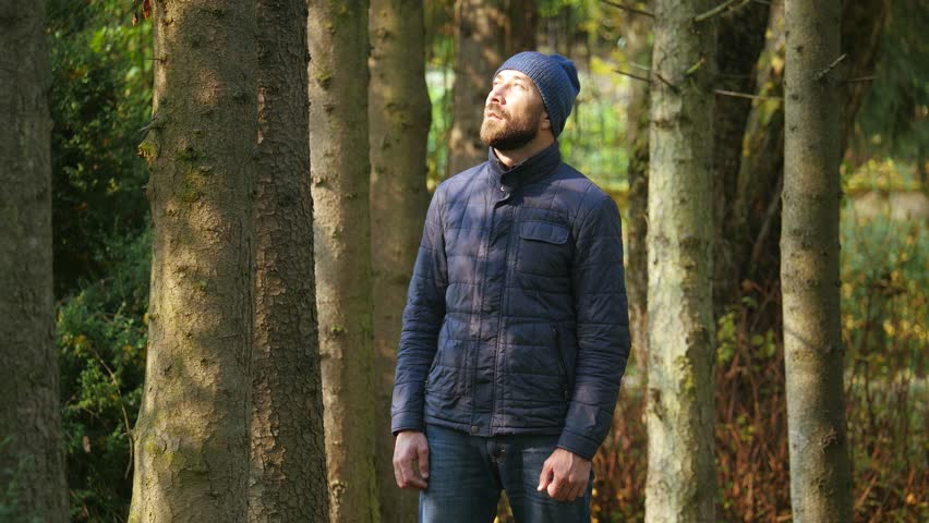 Happy Young guy enjoying sunlight in city park. bearded man standing in a outerwear and knitted hat outdoor #1008627937