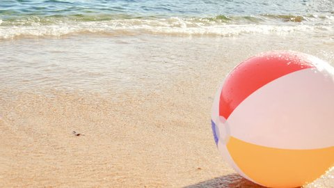 Beach Ball at the Mercy of the Waves. The sea dragging a beach balloon and returns it to the shore.