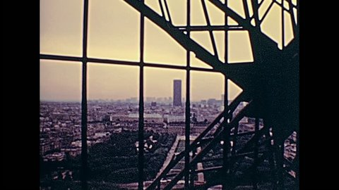 PARIS, FRANCE - CIRCA 1976: Tourists in 70s dress, descending the stairway from the observation aerial view of Paris from Eiffel Tower. Historic archival footage in Paris city of France in 1970s.