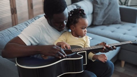 Close up view of adorable little baby-girl sitting on her father's knees and actively stroking the guitar, as if she plays it. Positive emotions, family bonds. Cozy living room. Slow motion