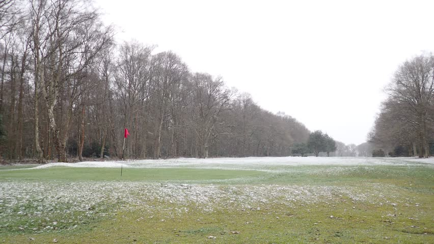 Golf course green during snowfall, Hertfordshire, UK