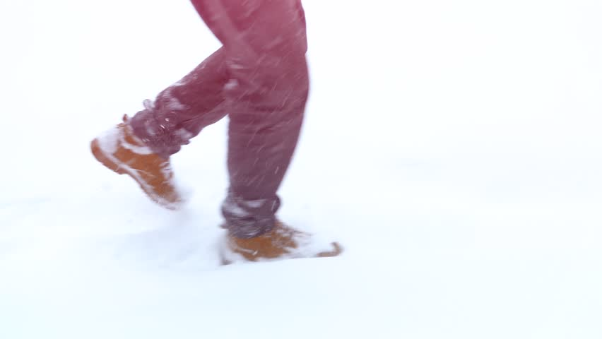 Walking feet in boots on a winter landscape in slow motion, a winter walk in the mountains, holiday vacation tourism, falling snow