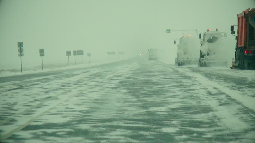 Movement of the car forward on the snow-covered Siberian route in a stream of trucks, at squally lateral wind | Shutterstock HD Video #1008713887