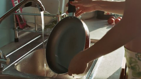 closeup woman with red manicure rinses frying pan under tap against bright sunlight through window