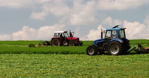 Mowing with a modern agriculture machine - tractors with mowers on the big farm field