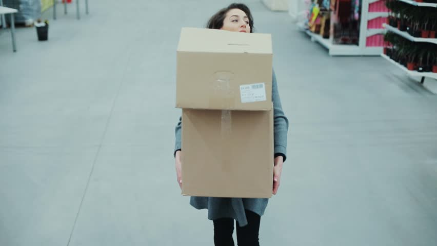 Attractive woman carries heavy boxes heavily inhaled hurry in a supermarket thinking shopping internet buy technology hypermarket shop mall smartphone grocery market girl food customer slow motion