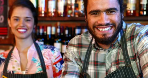 Portrait of smiling barmaid and barman at bar counter in pub