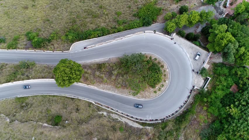 Aerial moving up above hairpin turn also called hairpin bend hairpin corner named for its resemblance to a hairpin bobby pin is bend in a road with a very acute inner angle vehicles driving over road