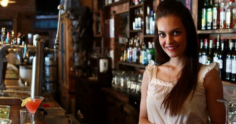 Portrait of barmaid cleaning bar counter in pub