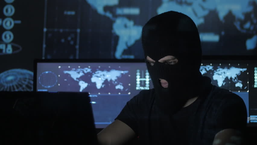 Dangerous hacker in the mask tries to enter the system using codes and numbers to find out the security password. The concept of cybercrime.   Shutterstock HD Video #1008776867