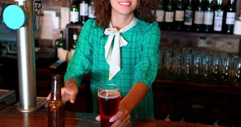 Barmaid pouring beer in a glass at bar counter in pub