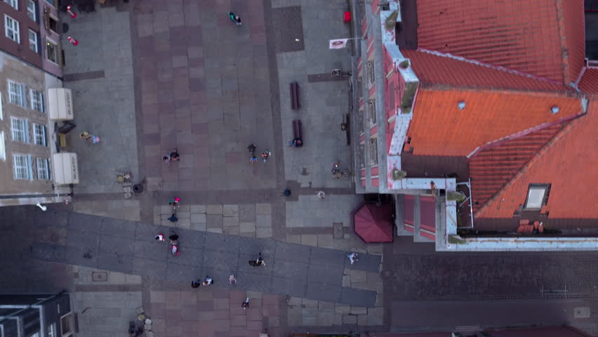"Drone shot in the evening time in Gdansk old town. Relaxed people walking cosy Long Lane ("" Dluga"" ) in the summer time. Historical Green Gate and the fountain of Neptune. 