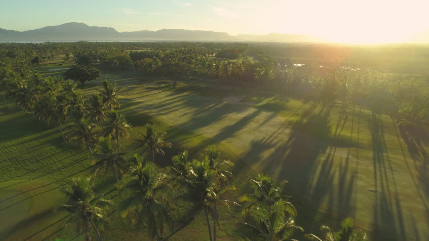 AERIAL LENS FLARE: Cinematic view of empty golden-lit golf course on the exotic island. Flying over fancy tropical golf range in Fiji during the low season. Breathtaking sunset shining on golf resort.