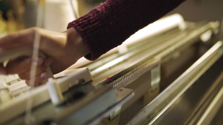 Female hands making knitted texture on weaving machine. Close up process manufacturing textile on knitting machine at modern factory. Handmade weaving fabric on loom machine