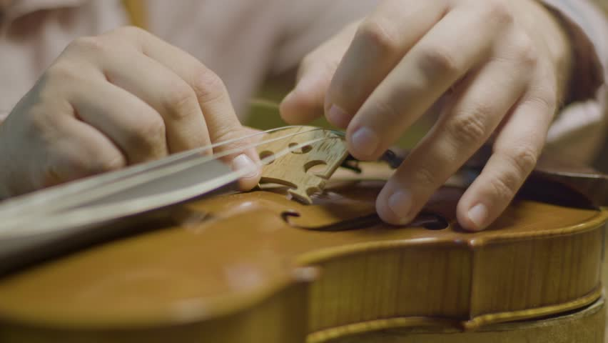 Slow motion close up of a craftsman placing the bridge for the violin strings