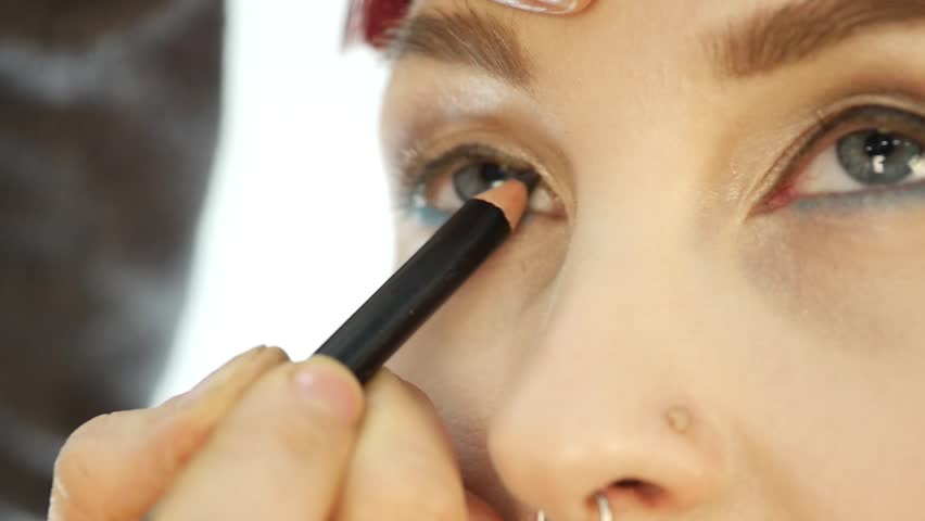 Professional make-up artist applying eyeliner on eye. makeup and fashion concept