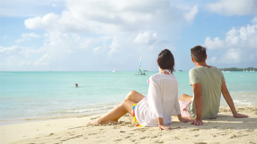 Young couple on white beach during summer vacation. Happy lovers enjoy their honeymoon at exotic island