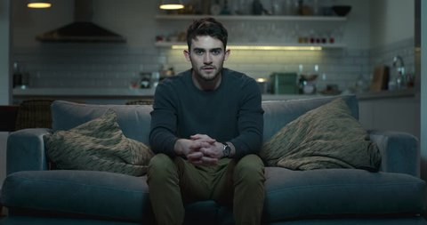Young man sitting on the edge of a couch watching a scary movie.