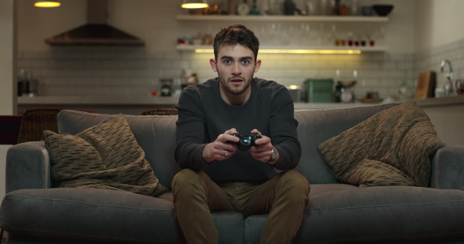 Young man sitting on couch playing video games. | Shutterstock HD Video #1008851207