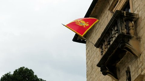 red flag of Montenegro hangs on a house with a balcony in Kotor