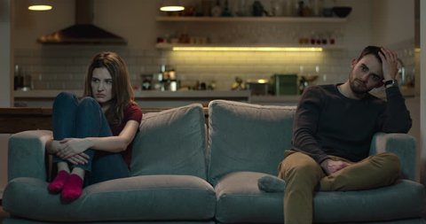 Unhappy couple on the sofa sit apart and ignore each other after disagreement