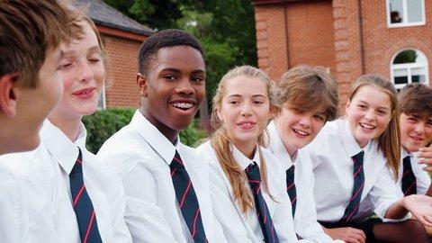 Teenage Students In Uniform Socializing Outside School Buildings