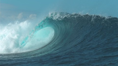 SLOW MOTION CLOSE UP: Breathtaking turquoise barrel wave crashes on a perfect summer day at the sea. Beautiful glistening tube wave crashes in the middle of the breathtaking ocean. Powerful water rush