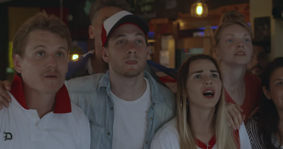 British football fans cheering while watching televised match in sports bar, slow motion #1008892337