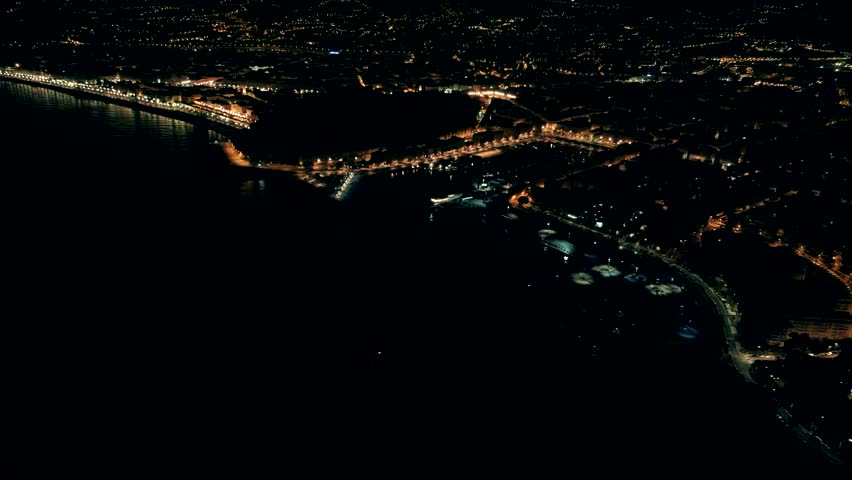 Night aerial view of illuminated Nice town in France. Flight over Nice marine port.