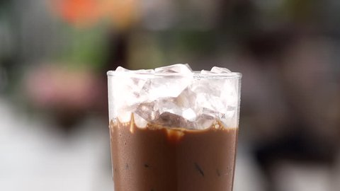 close up pouring milk to glass of ice coffee