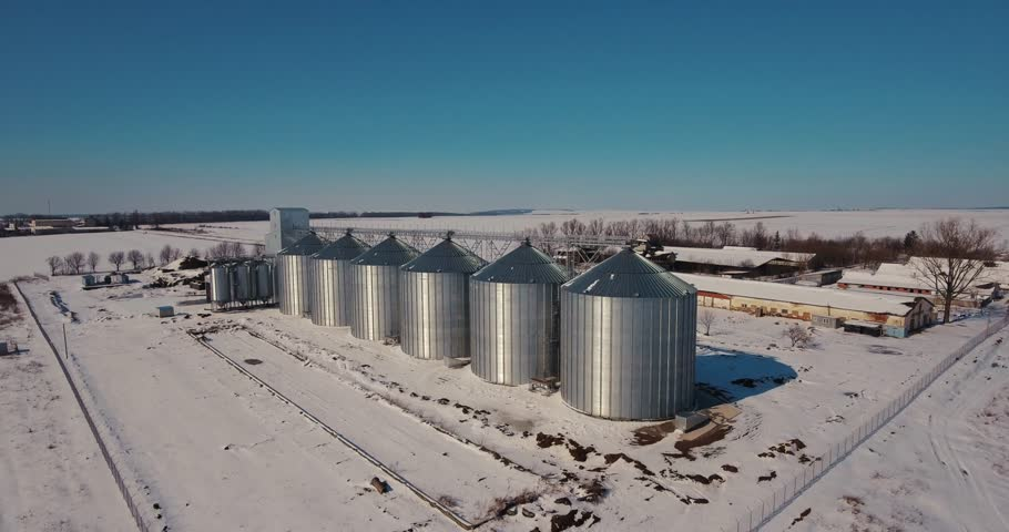 Agriculture industry, manufacturing plant . Agriculture grain silos storage tank. Modern large granary. Large metal silos. Elevator and factory. Winter Sunny day, the blue sky