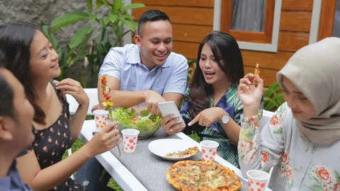 Group of friends enjoying meal at outdoor party in backyard one person showing his mobile phone