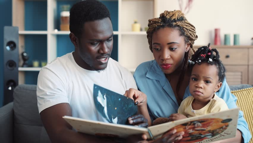 NEW YORK - April 5, 2017: Happy young parents sit together on the sofa and read a book to their adorable daughter, discuss the illustrations. Fairy tale, having fun, childhood memories | Shutterstock HD Video #1008976727