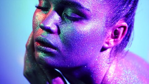 High Fashion model woman in colorful bright sparkles and neon lights posing in studio, portrait of beautiful sexy girl, trendy glowing make-up. Art design colorful make up. Glitter Vivid makeup 4K